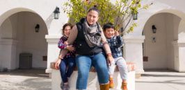 Angela with her two children sit outside of Casa San Juan