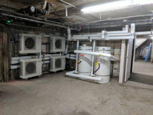 Heat Pump Water Heaters at 205 Jones Street apartments white heat pumps in basement