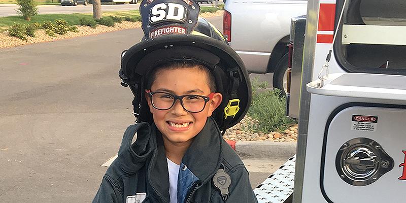 kid in firefighter helmet smiling
