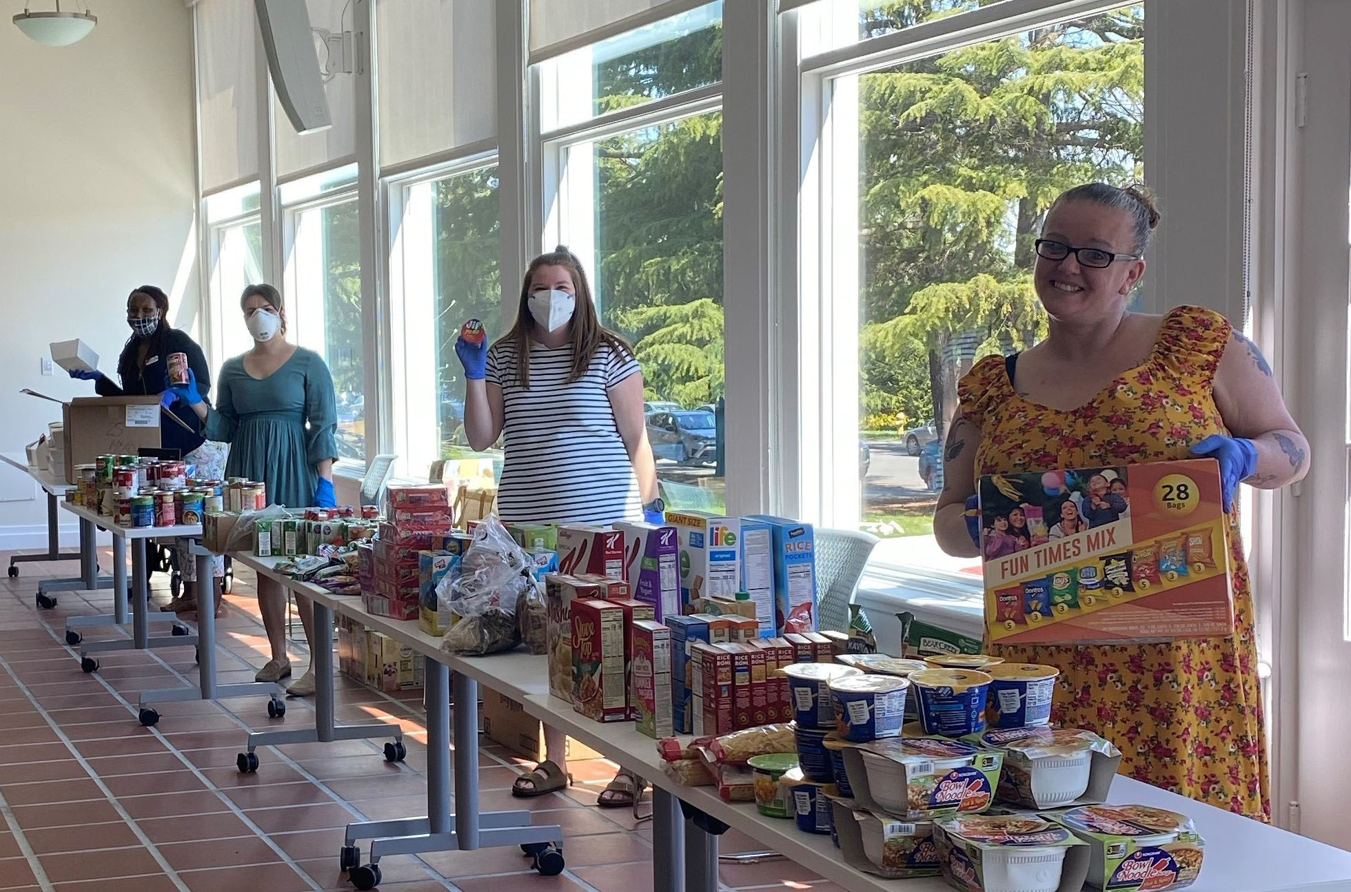Resident Service staff smilling in masks behind food tables