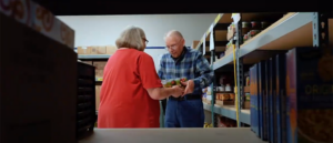 A senior woman handing a senior man some food in a food pantry