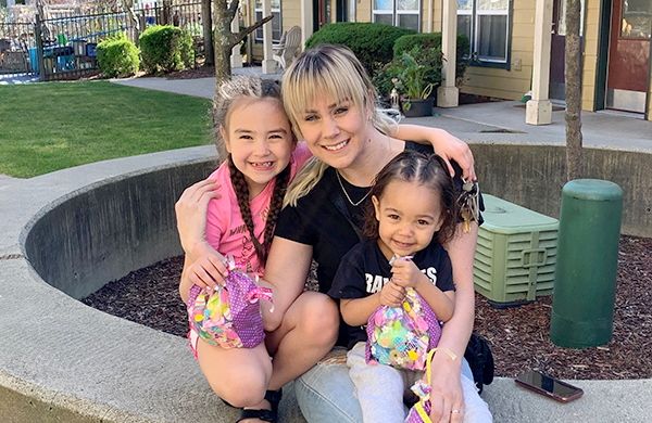Mom with two young daughters at Mercy Housing Northwest community